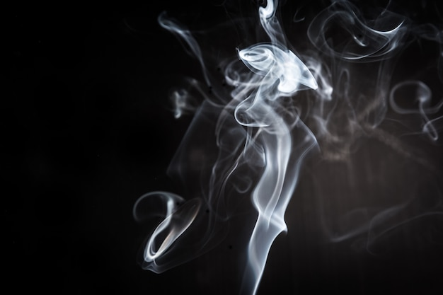 Abstract smoke swirls on black background