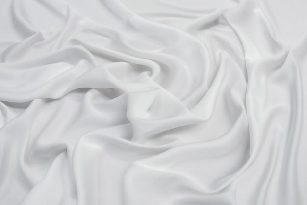 Абстрактная гладкая белая ткань, шелковая или атласная текстура, мягкая с плавными волнами.