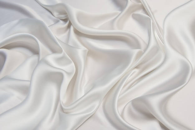 Abstract smooth white fabric silk or satin texture soft background with flowing waves.
