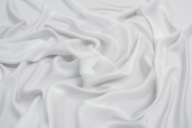 Abstract smooth white fabric silk or satin texture soft with flowing waves.