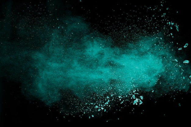 Abstract splash of green colored powder on black background.green powder explosion.