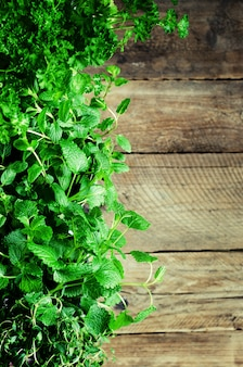 Abstract spring or summer concept. organic herbs (melissa, mint, thyme, basil, parsley) on wooden background with sunlight and sunny leaks.