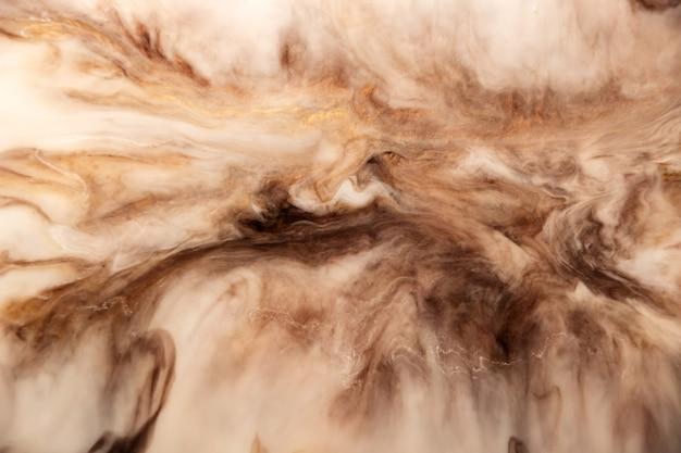 Абстрактные пятна от застывшей жидкости эпоксидной смолы имитация натурального камня. коричневый, золотой, белый и бежевый цвета.
