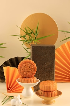 Abstract still life mid autumn festival snack moon cake on cream  background with young bamboo tree, selected focus, copy space for text