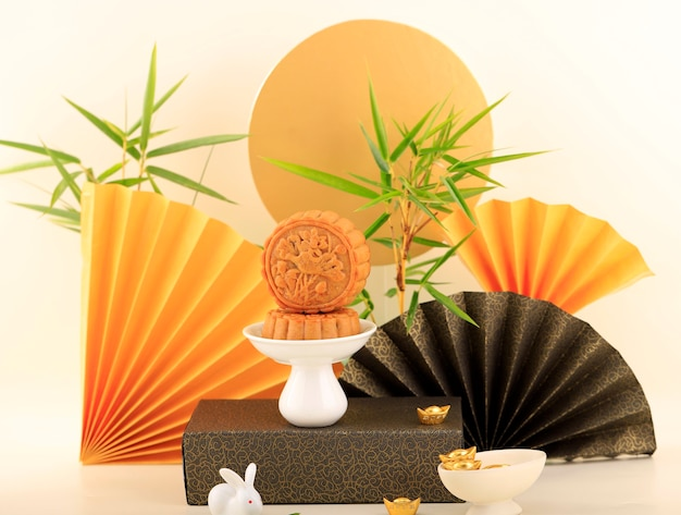 Abstract still life mid autumn festival snack moon cake on cream  background with young bamboo tree