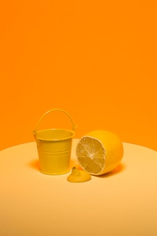 Абстрактный натюрморт с желтым ведром и лимоном на апельсине