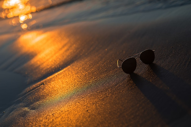 해변 모래와 물에 황금빛 일몰 빛과 선글라스가 있는 추상적인 여름 배경