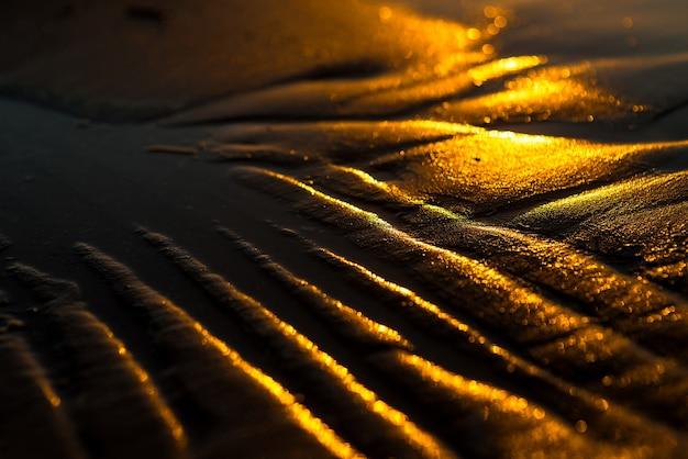 해변 모래와 물에 황금빛 일몰 빛이 있는 추상적인 여름 배경