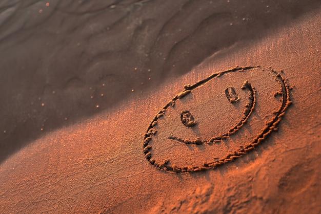해변 모래에 황금빛 일몰 빛이 있는 추상적인 여름 배경과 웃는 이모티콘 얼굴