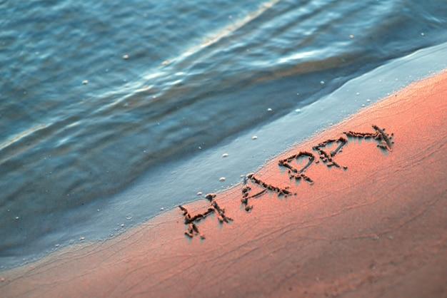 해변 모래에 황금빛 일몰 빛이 있는 추상적인 여름 배경과 행복한 단어