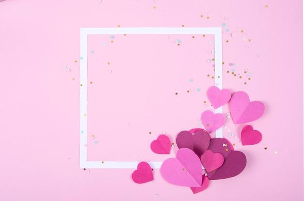 Абстрактная поверхность с бумажными сердечками и пустой белой рамкой на день святого валентина
