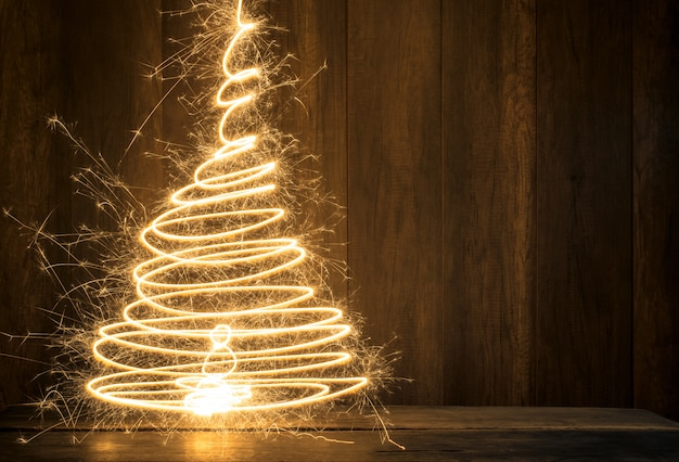 Abstract symbolic christmas tree created using sparklers with wood table and wood wall background