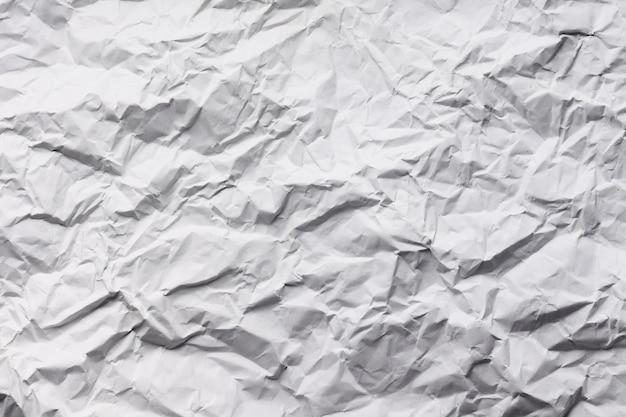 しわの白い紙の抽象的なテクスチャの背景