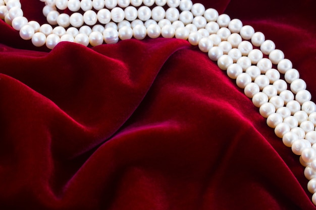 Abstract texture of  draped  dark red velvet background with pearls
