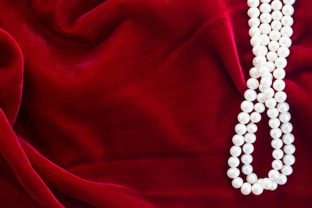 Abstract texture of  draped red velvet background with pearls