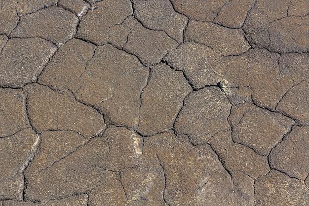 Абстрактная текстура высушенной треснутой выжженной земли. глобальное потепление и нехватка воды на планете концепции. затвердевшая серая поверхность земли для фона или графического дизайна.