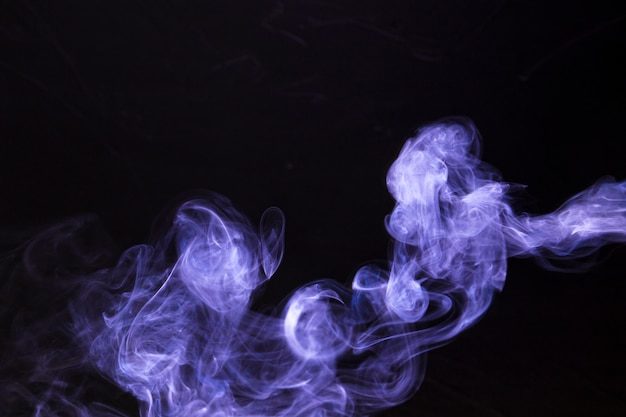 Abstract and texture of purple magic smoke on black background