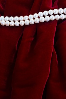 Abstract texture of  soft red velvet background with pearl jewelery