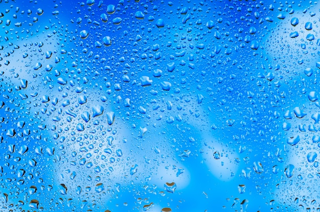 Abstract texture. water drops on glass with sky and clouds