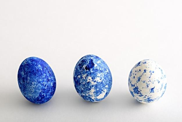 今年の色で3つのイースターエッグを抽象化します-白い背景にグラデーション効果を持つクラシックな青