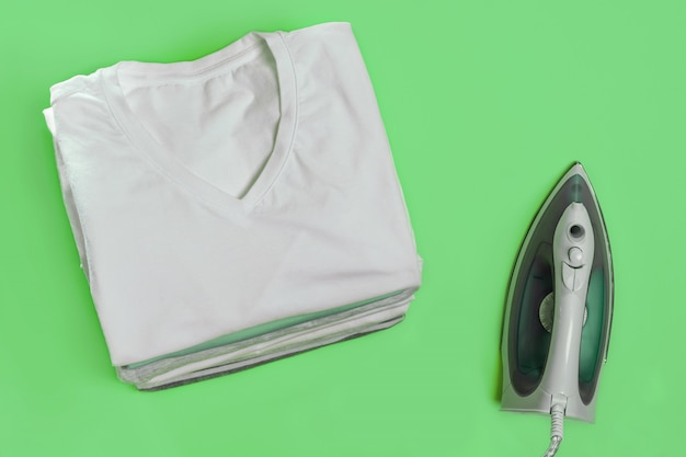 Abstract top view of iron and clothes for ironing on green background.