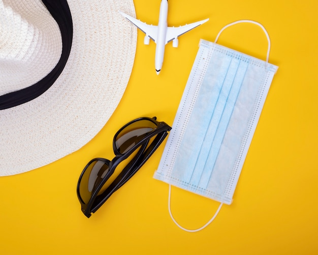 Abstract travel restriction face mask, sunglasses and hat.