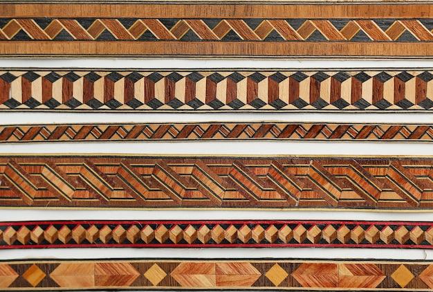 ウッドの背景上の抽象的な部族のパターン