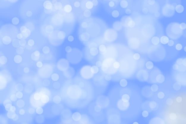 ボケ味の焦点がぼけたぼかしで抽象的なきらめく明るい水色の背景。