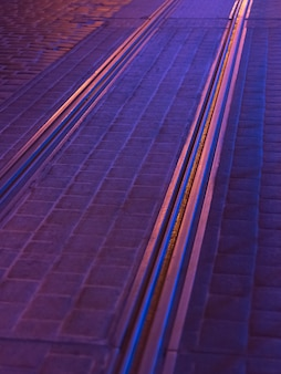 紫の抽象的な都市の背景。街の夜のイルミネーションに照らして路面電車の線路がある道路
