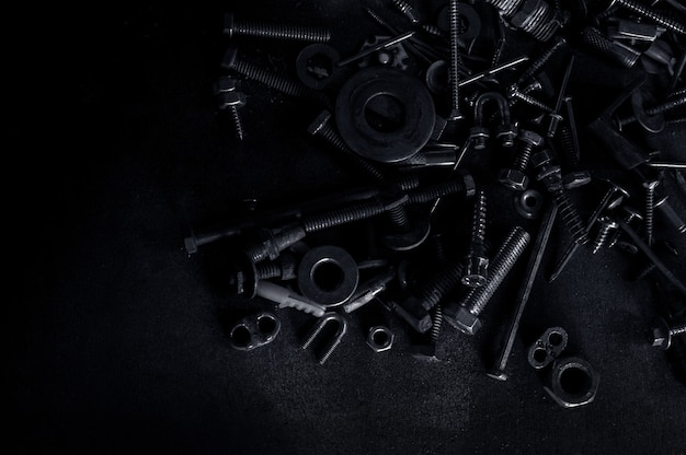 Abstract of used metallic screw nuts and nail bolts on dark background