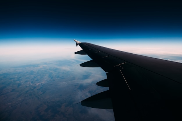 Abstract view of a wing of the aircraft in the space above the sky. looking through window aircraft during flight