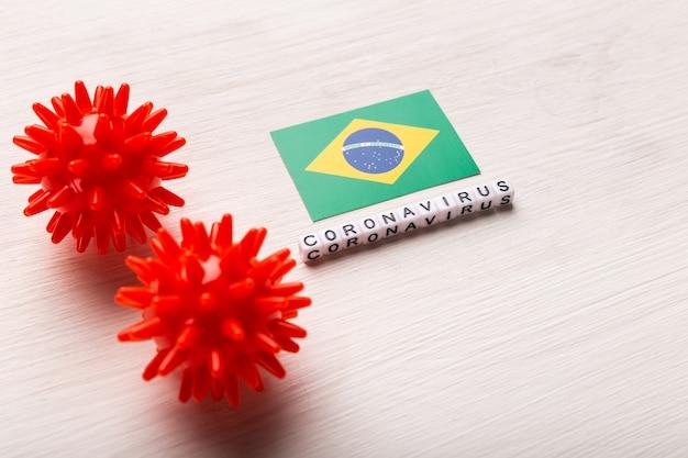 Абстрактная модель штамма вируса коронавируса ближневосточного респираторного синдрома 2019-ncov или коронавируса covid-19 с текстом и флагом бразилии на белом фоне. концепция защиты от пандемии вируса.