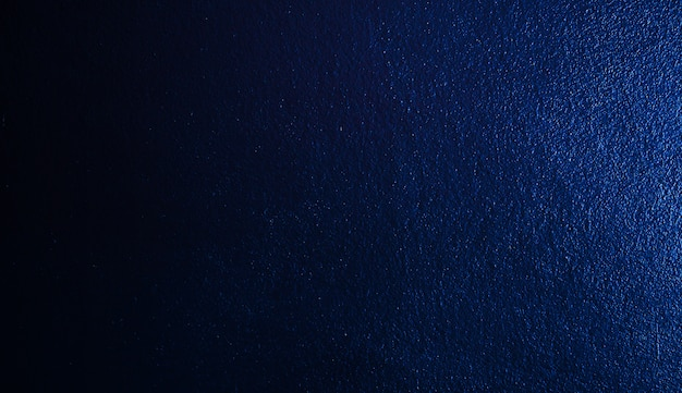 Abstract wall wallpaper with blue gradient black dark cement wall.