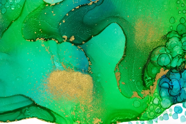 Abstract watercolor ink green and blue texture with gold glitter.