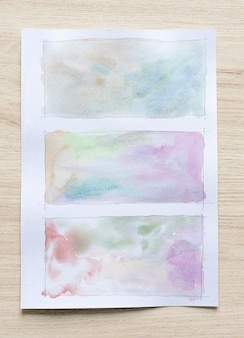 Abstract watercolor stains background on white paper sheet with wood background. close-up.