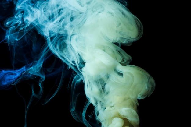 Il fumo denso bianco e blu astratto turbina su fondo nero