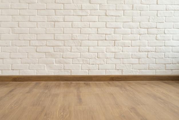 抽象的な白いレンガの壁面の質感と茶色の木製の床の背景