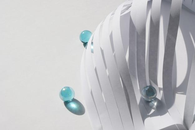 Абстрактные полосы белой бумаги и синие шарики