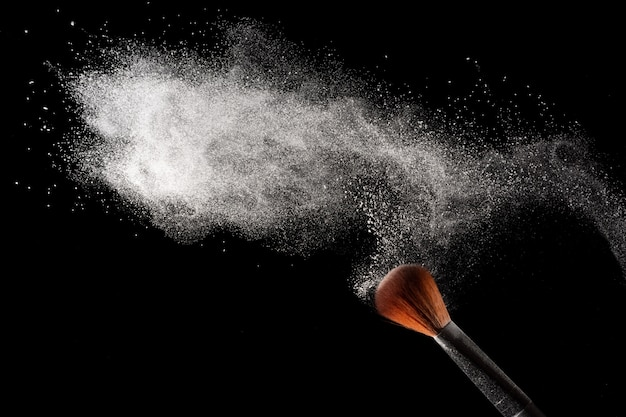 Abstract white powder dust explosion on black background.