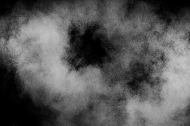 Abstract white powder explosion against black background.white dust cloud in the air.