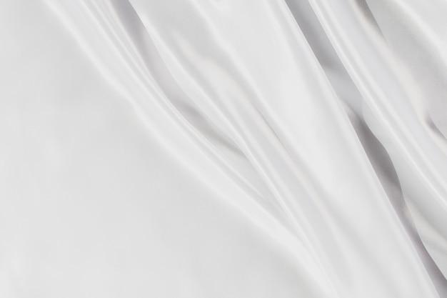 배경을 위한 추상 흰색 새틴 실크 천, 주름이 있는 패브릭 섬유 드레이프. 부드러운 파도가 바람에 흔들립니다.