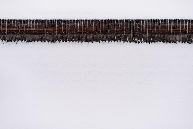 雪と抽象的な冬の背景。家の屋根の下のつららの境界線