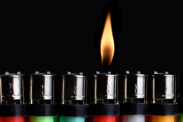 Abstract with colored lighters and a single flame