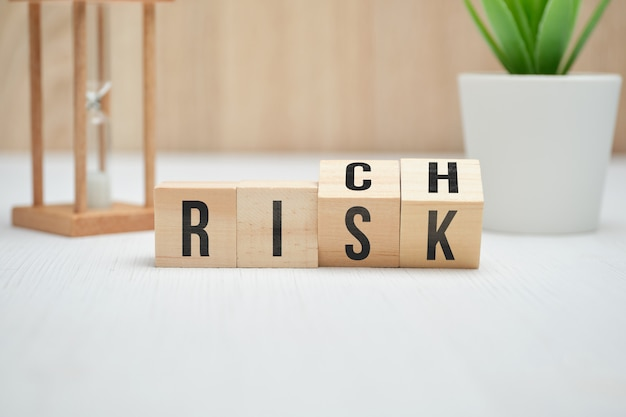Abstract words risk and rich on wooden cubes.