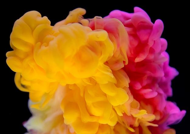 抽象的な黄色とピンクの色が水に落ちる
