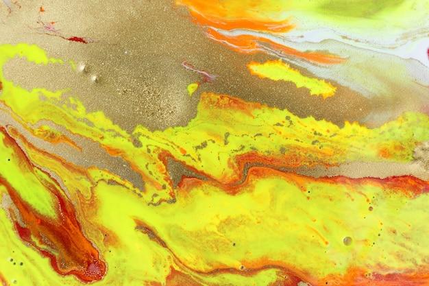ゴールドのキラキラ液体ペイントの背景を持つ抽象的な黄色の大理石のパターン