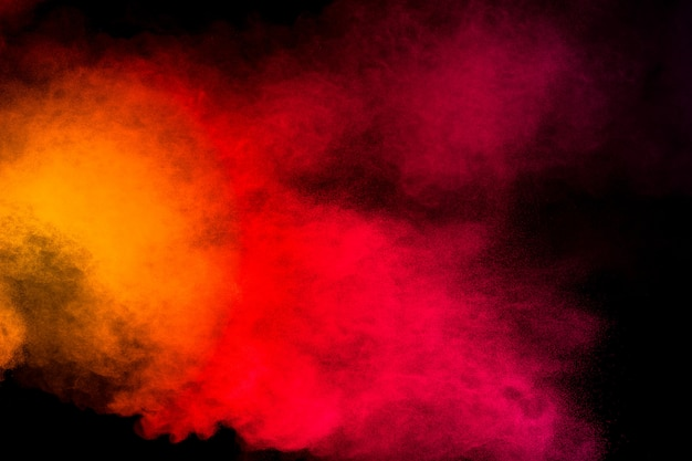 黒の背景に黄色オレンジ色の粉末爆発を抽象化します。黄色オレンジ色のほこり粒子スプラッシュの動きを凍結します。