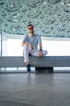 Абу-даби, объединенные арабские эмираты, 20 мая 2020 г .: молодой человек сидит в лувре в абу-даби и изучает искусство.
