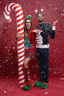 사탕 지팡이 옆에 서있는 부부와 함께 크리스마스 시간에 눈이 많이