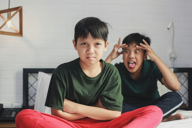 Abused child by elder brother sitting with crossed arms on a bed